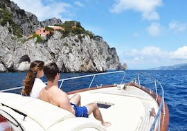 A couple is enjoying the sun during the private boat trip from Sorrento to Capri with Lubrense Boats Costiera Amalfitana.
