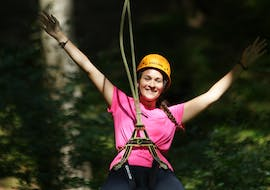 A girls smiles into the camera while ziplining in the flying fox park operated by Spirits of Nature in Allgäu.