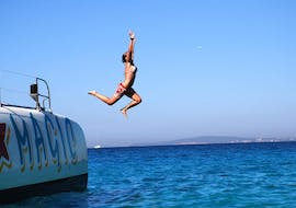 A woman is jumping from the boat of Magic Catamarans into the water while on their catamaran tour around the bay of Palma de Mallorca.