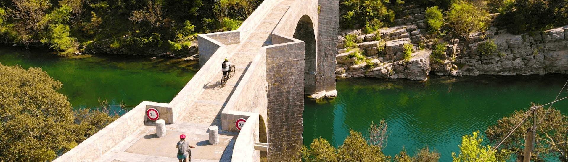 Tourists are passing by Pont du diable during the E-Mountain Bike Rental in Saint-Jean-de-Buèges with Le Garrel Hérault