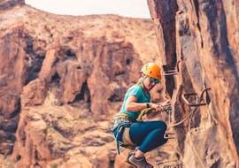 A woman climbs a Via Ferrata in the Barranco del Aguila in Gran Canaria with Climbo.
