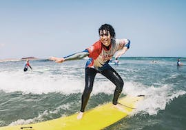 A girl enjoys her first wave during the surfing lessons on Famara Beach for Beginners with Red Star Surf Lanzarote.