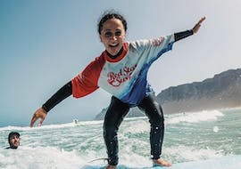 A girls has lots of fun on the board during the surfing lessons on famara beach for intermediates with red star surf Lanzarote.