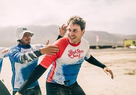 A man learns the surfing technique from one of the instructors of red star surf lanzarote during his private surfing lessons on Famara Beach.