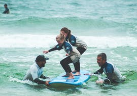 Two Kids enjoy their time during the surfing lessons for kids on the beach of Nazaré with Surf4You.