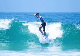 A guy surfs a big wave during his private surfing lessons with Surf4You in Nazaré.