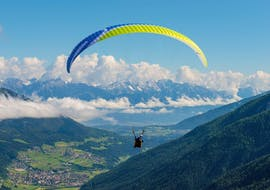 A paraglider gliding through a spectacular panorama during the tandem paragliding in Innsbruck with Paragliding Tirol.