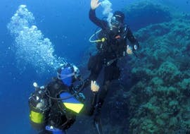 A student and his instructor are communicating underwater during the FFESSM Level 1 Beginner Diving Course with European Diving School Hyères.