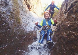 A girl sliding while canyoning in the Ribeira das Cales with Madeira Adventure Kingdom.