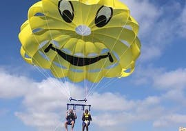 Two people enjoy a parasailing ride in St George's Bay with Sun & Fun Watersports.