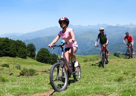 A young girl is cycling across a meadow with her bike rented from the bike hire at Skischule & Bikeverleih AGE Ötz-Hochötz in the Oetztal Valley.