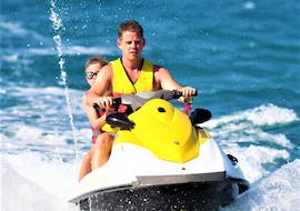 Two people enjoy a jet ski ride at Ammourada Beach with H2O Water Sports Heraklion.