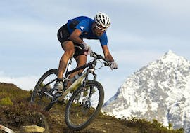 A cyclist can be seen riding down a mountain on a bike rented from the bike hire shop at Skischule & Bikeverleih AGE Ötz-Hochötz in the Oetztal Valley.