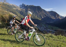 A man and a woman are riding along a mountain trail on their e-bikes from the e-bike hire shop Skischule & Bikeverleih AGE Ötz-Hochötz in the Oetztal Valley.