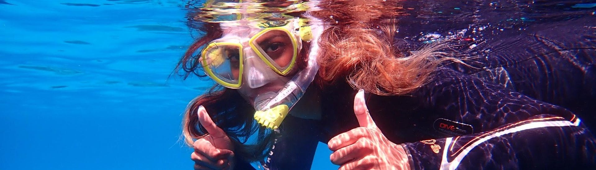 During the Snorkeling Trip to Cala Delta Nature Reserve with Diving and Adventure Mallorca, a young woman is snorkeling in the crystal clear water.