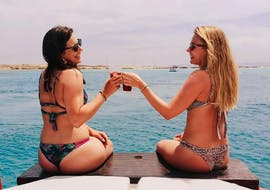 Two girls have a toast during a sunset boat trip to Formentera with Drinks together with Ibiza Nautical Excursion.