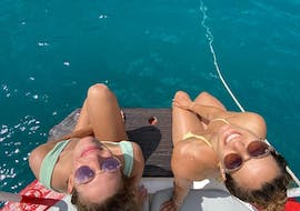 Two girls sunbathe during a boat trip in the South of Ibiza with snorkeling together with Ibiza Nautical Excursion.