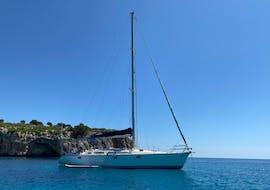 A sailing boat navigates around the east coast of Mallorca with Let's Sail Mallorca.