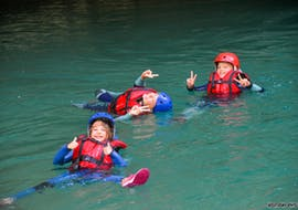 Kids are floating in the river during their River Trekking Tour in Pont de Tusset in Verdon for Families with Feel Rafting.