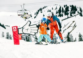 An instructor and a child during their kids ski lessons for beginners with ski school Warth Arlberg Snowsports in Warth.