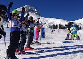 A group of children cheering during kids ski lessons for beginners with ski school Warth in Warth-Schröcken.