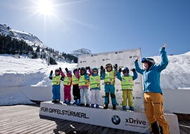"""A group of little skiers cheering during their kids ski lessons """"Bambini"""" for all levels with skischule Warth in Warth-Schröcken."""