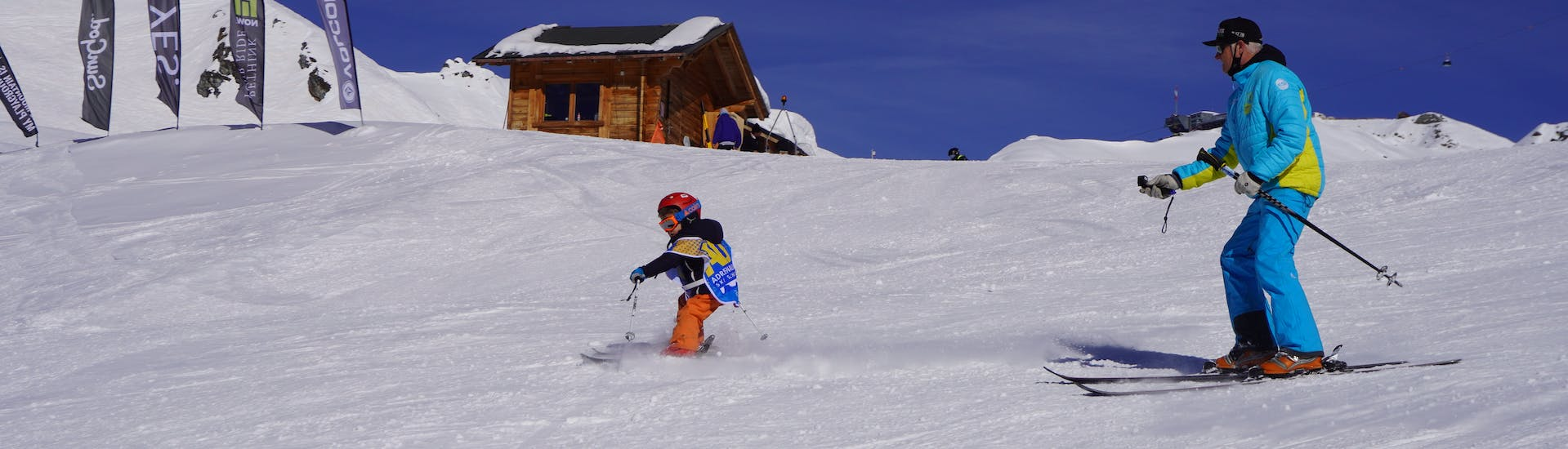 An instructor guides his student during a private ski lesson for kids with Adrenaline Verbier.