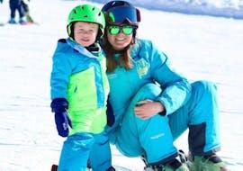 Un jeune skieur est très heureux d'être avec sa monitrice durant un cours particulier de ski pour enfants avec Adrenaline Verbier.