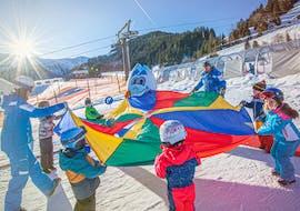 """Een groep kleine kinderen is aan het spelen tijdens hun skilessen voor kinderen """"miniclub"""" bij skischool Bad Hofstein."""