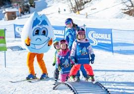Een groep jonge kinderen leert skiën tijdens de skilessen voor kinderen voor beginners bij skischule Bad Hofgastein.