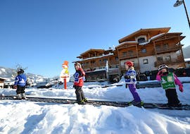 """Four kids on a magic carpet during their kids ski lessons """"Kids Club"""" for advanced skiers with Heli's Skischule Saalbach-Hinterglemm."""