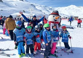 Kids are taking a group picture with their ski instructor from the ski school Ski Cool Val Thorens after their Kids Ski Lessons (5-12 y.) - Morning.