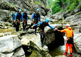 """A group of friends is having fun climbing down a small waterfall on their Canyoning Tour """"Jump & Splash"""" in the beautiful gorge Almbach together with the experienced guides of Frost Rafting & Canyoning Tours."""