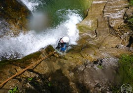 """During Canyoning """"Rocks & Ropes"""" for Sportive Beginners with Base Camp, a participant is roping down over a waterfall."""