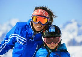 A kid with his ski instructor from the ski school Prosneige Méribel are smiling to the camera during theirPrivate Ski Lessons for Kids - High Season.