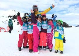 Un groupe de jeunes skieurs célébrent la fin de leur cours et les progrès qu'ils ont fait avec Villars Ski School.