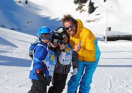 Trois enfants sont heureux d'avoir passé un cours particulier de ski avec un moniteur de la Villars Ski School.