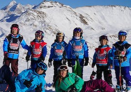 """A group of young skiers are posing for a picture at the top of the slopes with their ski instructors from the ski school Snocool during their Kids Ski Lessons """"Small Group"""" (5-12 years) - All Levels."""
