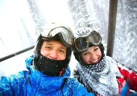 Two young adults smile on the cable car before the ski lessons for adults for beginners in the Schneesportschule Black Forest Magic Feldberg.