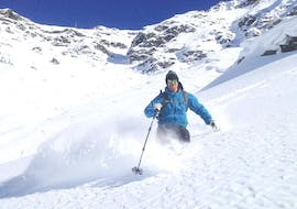 Under the guidance of an instructor from the ski school SnoCool, a skier is enjoying the fresh powder snow during the Private Off-Piste Skiing Lessons for Adults - Val d'Isère.