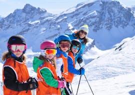 Des jeunes skieurs s'amusent lors de leur cours de ski pour enfants et sont ravis d'être enseignés par leur monitrice de l'ESI generation à Serre-Chevalier.