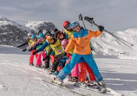 A row of children and their instructor in the snow during their kids ski lessons for all levels with Skischule Thommi in Nassfeld.
