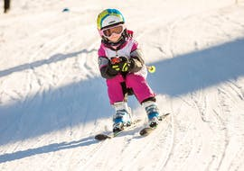 Children ski down the piste sporty and with bent knees during the Kids Ski Lessons (4-12 years) - All Levels with the ski school Thomas Spenzel.