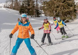 A group of children is skiing in line during their teen ski lessons for first-timers with skischule Thommi in Nassfeld.