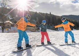 two instructors from skischule Thommi in Nassfeld are showing a child how to stand during its snowboarding lessons for beginners.