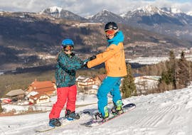 An instructor is helping a child to snowboarding during their private snowboarding lessons for all levels and ages with skischule Thommi in Nassfeld.