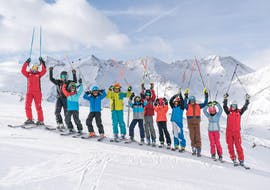 A large group of skiers is standing on the slopes cheering with their poles in the air during their Kids Ski Lessons (4-16 y.) for Advanced Skiers with skischule Obergurgl.