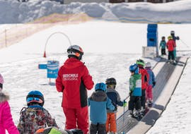 A ski instructor from skischule Obergurgel is showing a group of small children how to ride the magic carpet during their Kids Ski Lessons for Beginners with skischule Obergurgl.