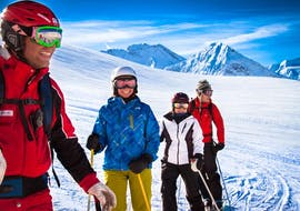 Three adult skiers and their instructor are standing in the snow, smiling during their Adult Ski Lessons for Beginners with skischule Obergurgl.