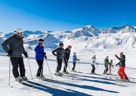 Au sommet des pistes un groupe de skieurs écoute les instructions de leur moniteur de ski de l'école de ski Evolution 2 Tignes pendant leur Cours de ski pour Ados & Adultes - Après-midi.